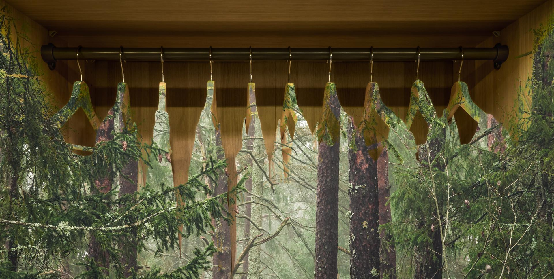 Clothes hanger with dresses in the forest. Concept for organic clothes, closet and sustainable fashion by B. Forenius