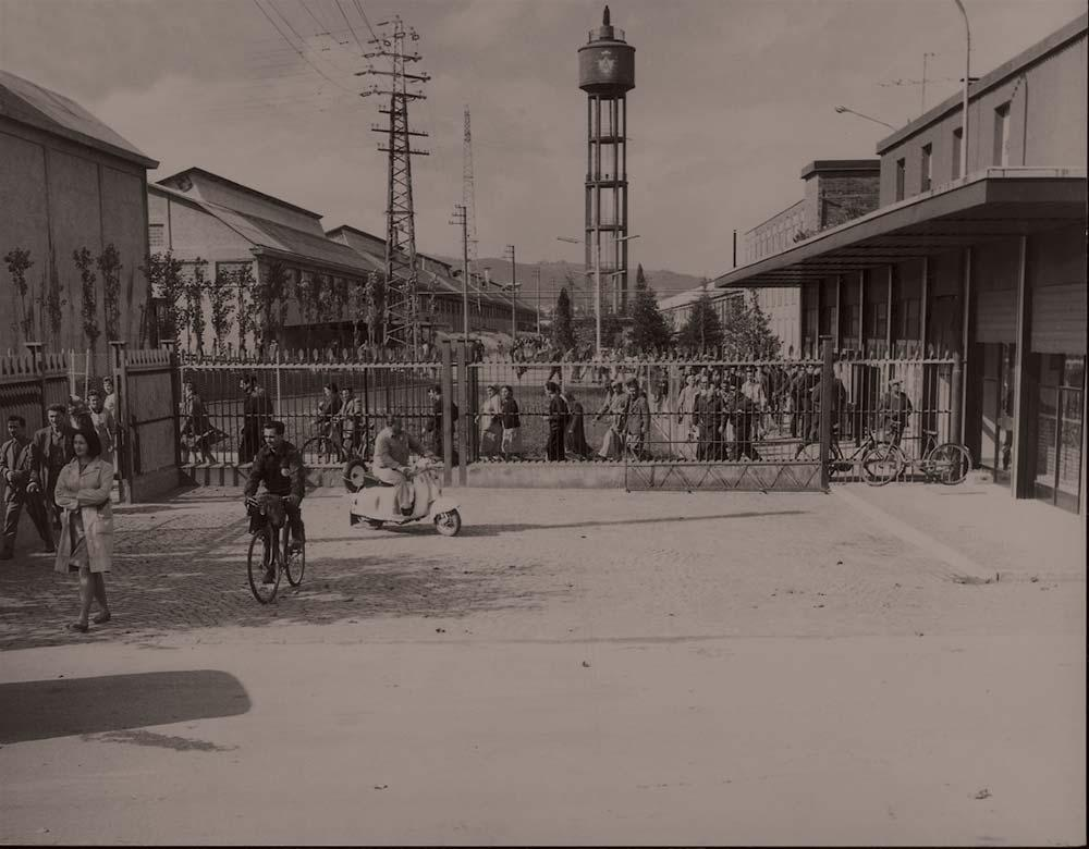 The Via Regina Pacis entrance, with people on foot, on bicycles and on Vespa scooters, in the '50s